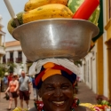 Colombian woman smiling as she carries a bowl of fruit on her head