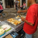 Man in a red t-shirt selling potato cakes from a roadside cart, Cartagena, Colombia