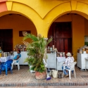 Locals sit by the store set out under the arches of a yellow building Cartagena, Colombia