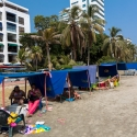 Families sitting in their beach tents on the Plaza Playa de Castillo Grande, Cartagena, Colombia