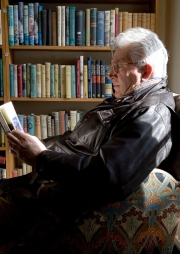 Older man reading in a armchair in a bookshop in Hay on Wye Engl