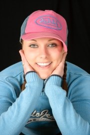 Pretty smiling young woman with good teeth wearing baseball cap