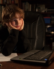 Young business boy in an office studying the laptop computer